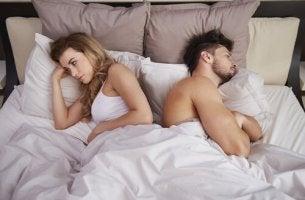 Sexuelle Anorexie - Ein Paar liegt frustriert und mit dem Rücken zueinander im Bett.
