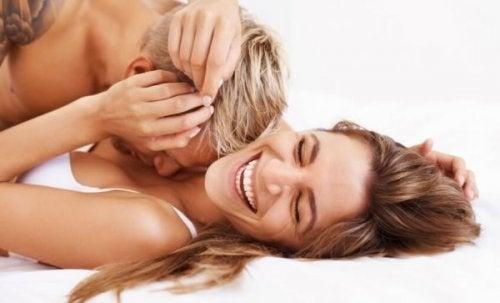 Partner umarmen sich, während sie im Bett sind.
