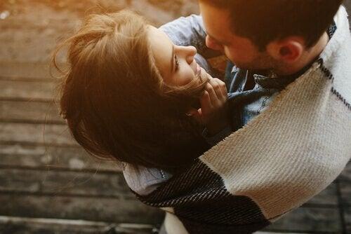 Ein junges Paar, das in eine Decke gehüllt ist, umarmt sich.