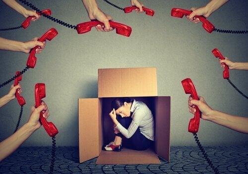 Eine Frau versteckt sich in einem Karton, während viele Telefone klingeln.