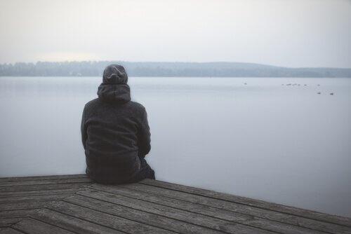 Eine Person sitzt auf einem Steg.