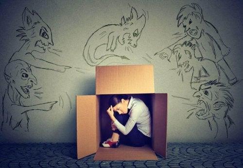 Eine Frau sitzt in einer Kiste. Um sie herum sind böse Figuren gezeichnet.