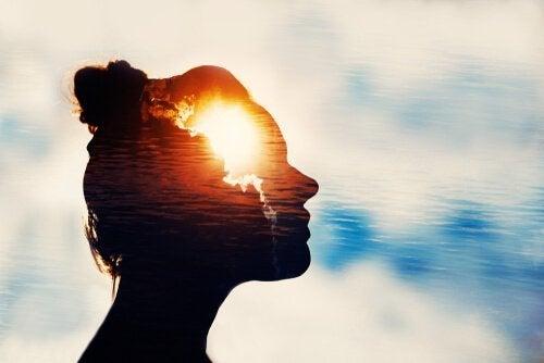 Eine Silhouette einer Frau vor blauem Himmel und Wolken.