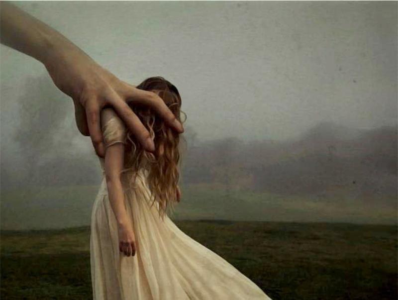 Eine junge Frau in weißem Kleid wird durch eine überdimensionale Hand gesteuert