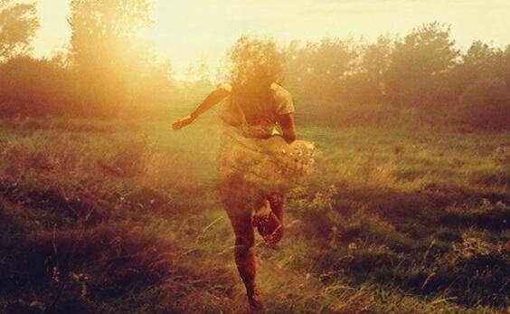 Frau rennt auf einem Feldweg in Richtung Sonne