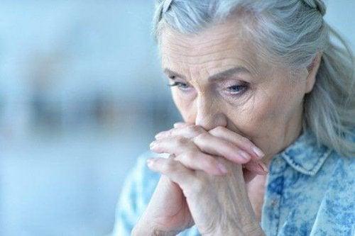 Seniorin kämpft gegen Niedergeschlagenheit, hält sich die Hände vor das Gesicht.