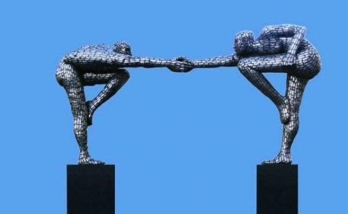 Eine Statue, die zwei Menschen zeigt, die sich an den Händen berühren.