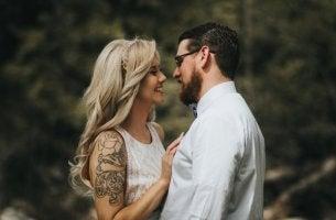 Stigmatophilie - Mann schaut verliebt auf seine tätowierte Frau