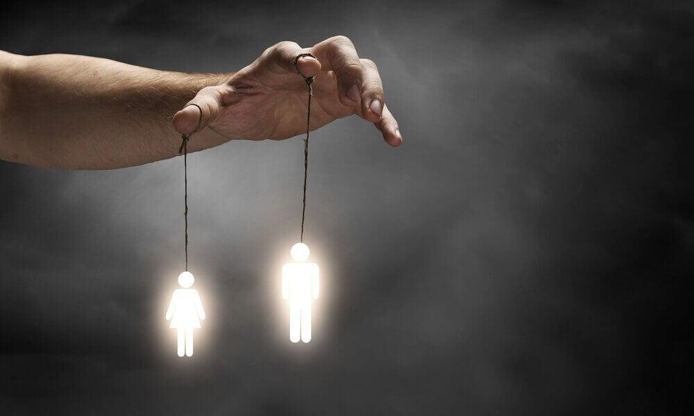 Menschliche Figuren hängen an einer Hand an Fäden