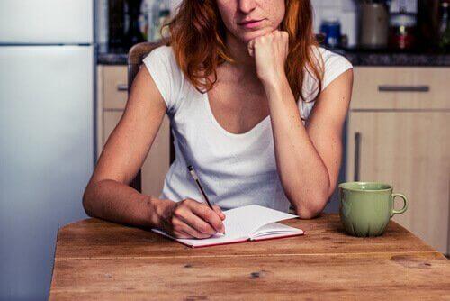 Frau schreibt Tagebuch am Tisch