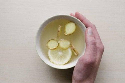 Eine Hand ist um eine Tasse Tee gelegt, der mit Ingwer und Zitrone gemacht ist.