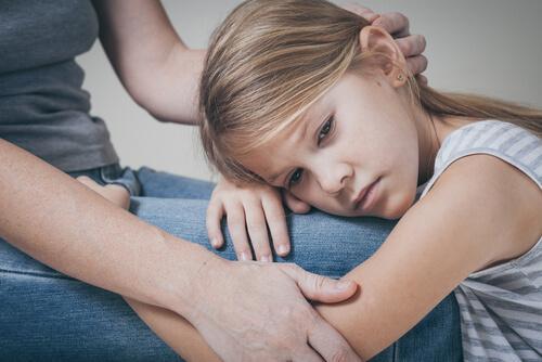 Traurige Tochter, die angstvoll auf dem Schoß ihrer Mutter liegt