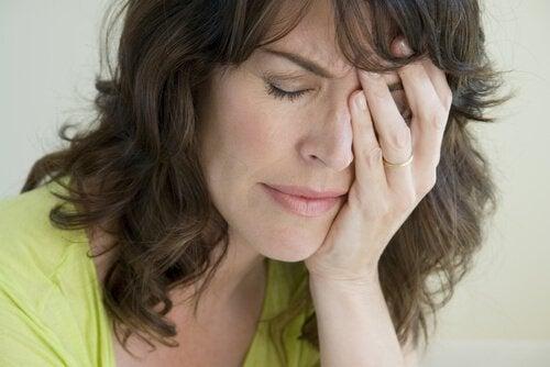 Ein traurige Frau denkt nach, während sie ihre Hand vor ihr Gesicht legt.