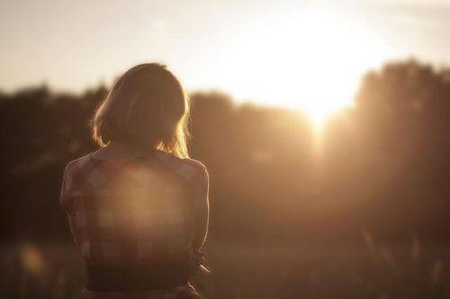 Eine traurige Frau betrachtet den Sonnenuntergang.