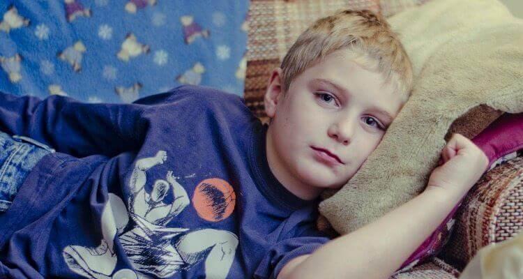 Junge liegt krank auf dem Sofa