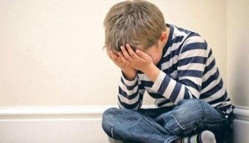 Für Psychosen prädisponiert? - Trauriger Junge, der auf dem Boden sitzt