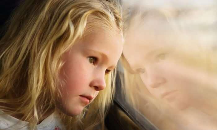 Trauriges Mädchen sieht aus dem Fenster