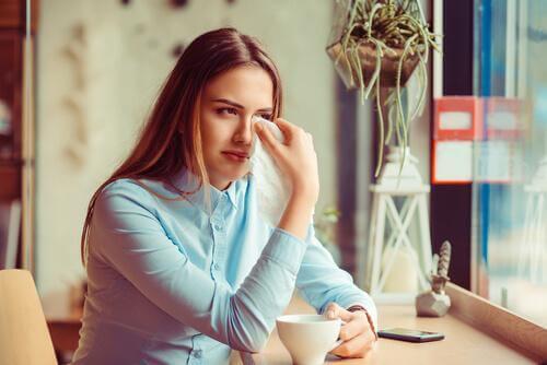 Weinende Frau sitzt mit einer Tasse am Fenster