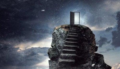Eine Treppe führt einen Felsen hinauf und endet vor einer Tür, die sich ins Nichts öffnet.