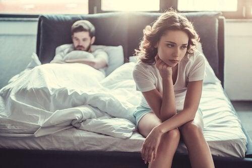 Ein Paar scheint sich gerade zu streiten. Der Mann schmollt im Bett und die Frau sitzt nachdenklich auf der Bettkante.