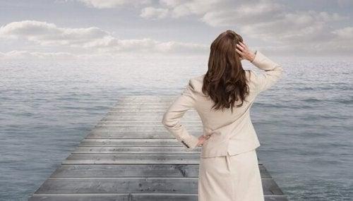 Eine Frau steht auf einer Brücke und schaut auf das Meer.