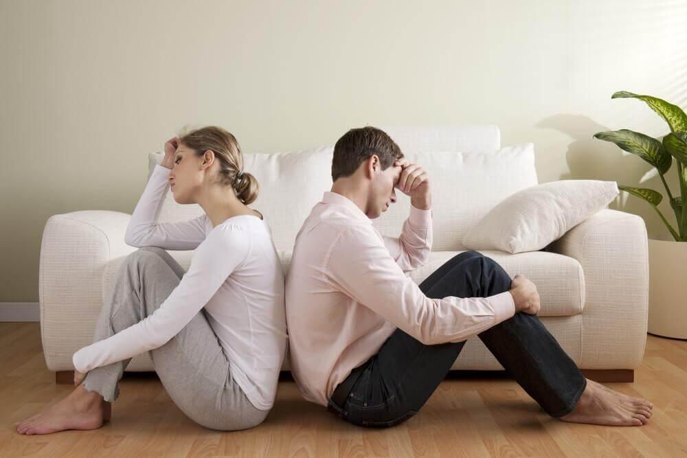 Paar sitzt Rücken an Rücken enttäuscht auf dem Boden
