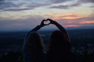 Wahre Freunde formen mit ihren Händen ein Herz.