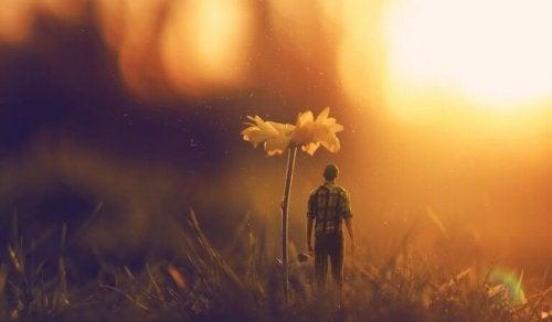 Winziger Mann steht neben einer Blume