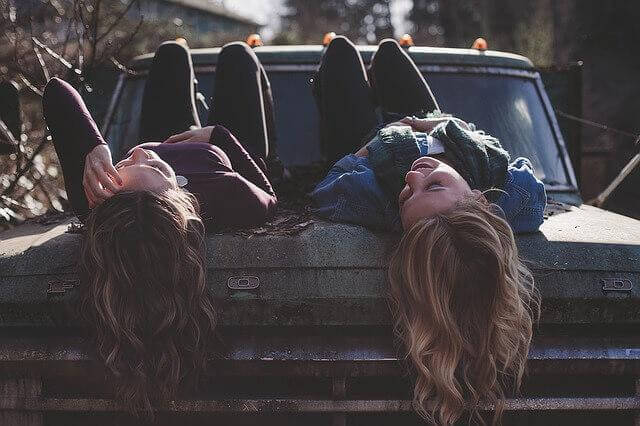 Zwei Freundinnen liegen auf einem Auto und schauen lachend in den Himmel