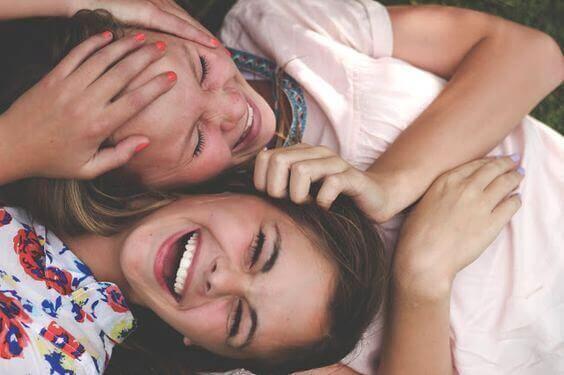 Lachende Freundinnen liegen nebeneinander