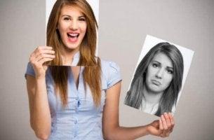 Zyklothymia - Eine Frau hält sich ein Foto einer lachenden Frau ins Gesicht. In der anderen Hand hält sie das Foto einer Frau, die traurig ist.