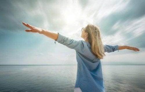 Frau mit ausgestreckten Armen am Meer