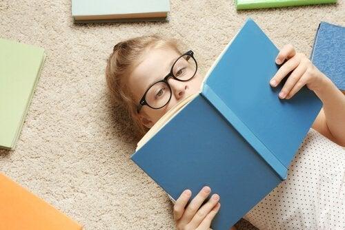 Kind liegt auf dem Boden und liest