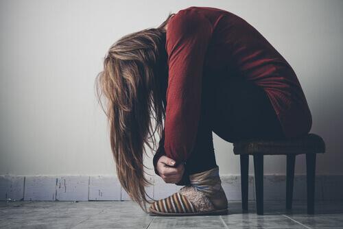Frau mit depressiver Stimmung sitzt zusammengekauert auf einem kleinen Stuhl