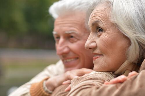 Älteres, zufriedenes Ehepaar schaut lachend in die Ferne
