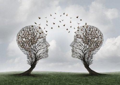 Zwei Bäume in der Form von Köpfen sind einander zugewandt und tauschen einen Vogelschwarm aus.
