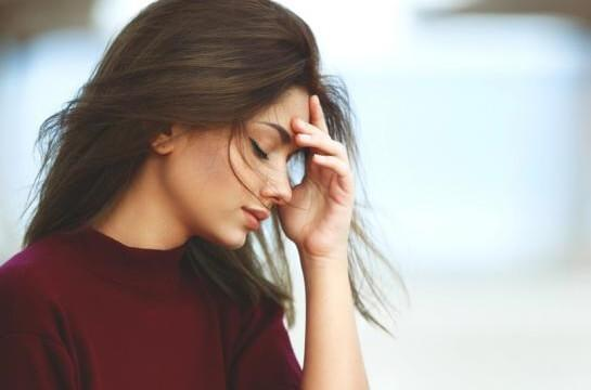 Frau mit Kopfschmerzen langt sich an den Kopf