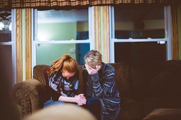 Zwei Frauen sitzen auf einer Couch und weinen.