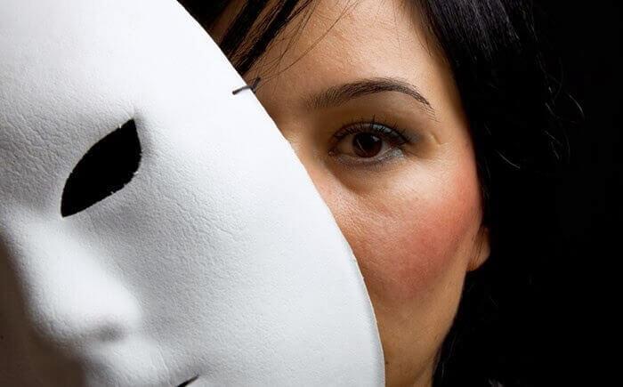 Frau schaut hinter einer weißen Maske hervor
