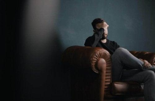 Ein depressiver Mann sitzt auf einem Sofa.