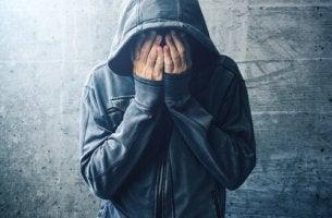 Drogensüchtiger Mann schlägt die Hände vors Gesicht