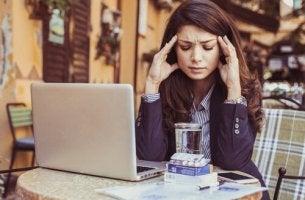 Eine Frau am Rechner versucht, emotionale Herausforderungen zu bewältigen.