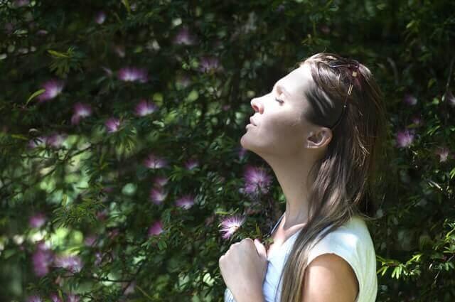Frau atmet mit geschlossenen Augen tief ein