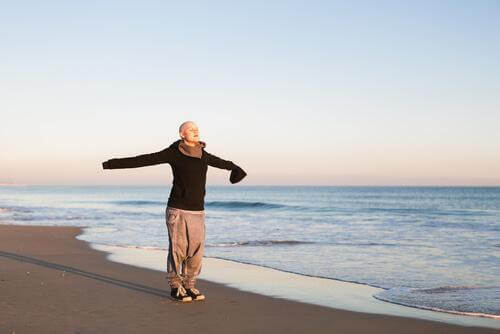 Entspannung für Frauen mit Brustkrebs: Eine an Krebs erkrankte Frau steht mit ausgestreckten Armen und verschlossenen Augen am Strand.