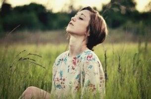Entspannungsübungen für den Geist - Frau meditiert auf einer Wiese