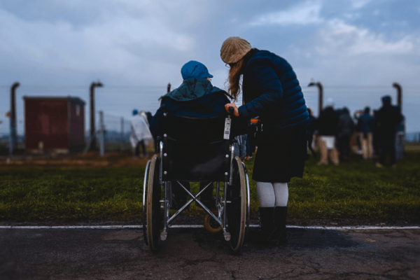 Ein Elternteil mit Kind im Rollstuhl