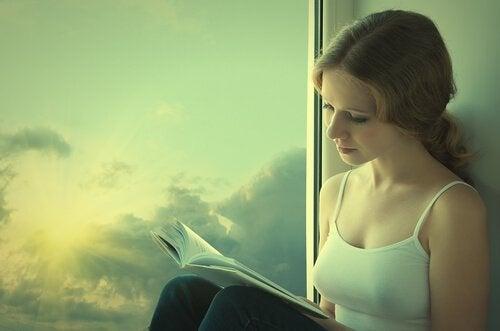 Frau, die neben einem Fenster sitzt und ein Buch liest