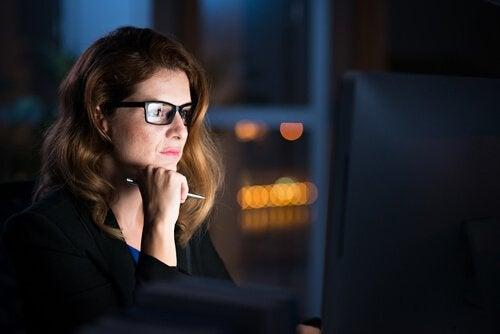 Eine Frau arbeitet nachts am Computer.