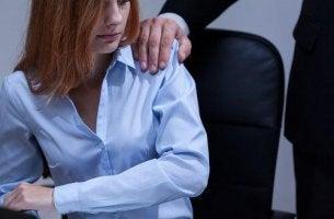 Eine Männerhand liegt auf der Schulter einer Frau, während sie an einem Schreibtisch sitzt.