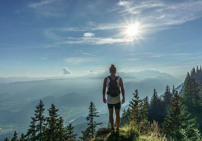 Ein Mensch steht auf einem Berggipfel und blickt in ein Tal.